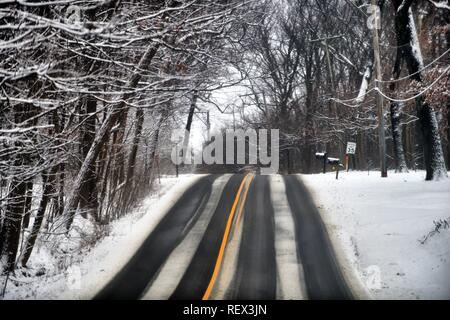 Wayne, Illinois, USA. A country highway during a snow shows evidence of slippery conditions as it crests the top of a hill. - Stock Photo