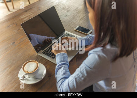Office woman in blue shirt working on laptop indoor the office - Stock Photo