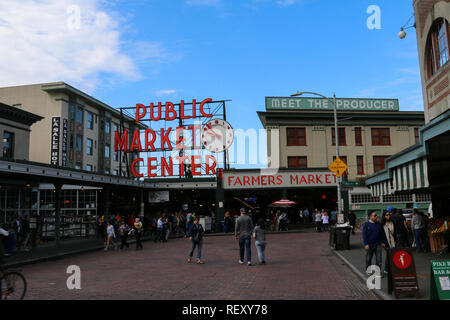 Iconic sign and entrance to the Pike Place Market in Seattle, Washington on a sunny day with blue sky and partial clouds, shoppers passing by - Stock Photo