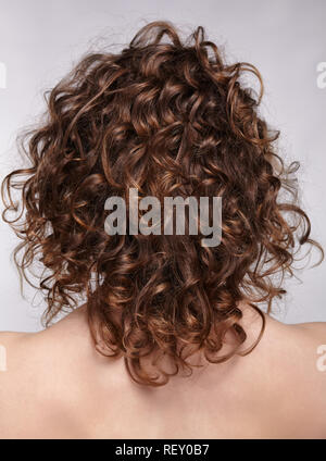 Woman from backside on gray background. Female with curly hair.