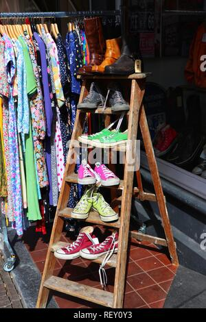 A colourful display of shoes and boots for sale outside a shoe shop in Amsterdam, Holland, presented in a quirky way on each rung of a step ladder. - Stock Photo