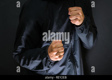 Violence and crime on the streets, digital glitch effect, victim is punched and mugged by aggressive violent man in hooded jacket, cctv security camer - Stock Photo