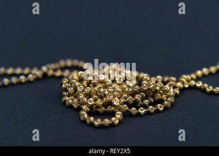 Gold necklace isolated on black background, macro closeup showing yellow golden chain links detail - Stock Photo