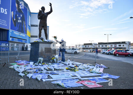 Flowers and tributes left by the statue of Cardiff City footballer Frederick Charles Keenor outside Cardiff City Football Club after a plane with new signing Emiliano Sala on board went missing over the English Channel on Monday night. - Stock Photo
