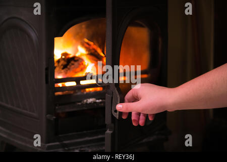 Human hand opening a door of the burning fireplace with wooden logs burning inside. Warm light, romantic, christmas like atmosphere - Stock Photo