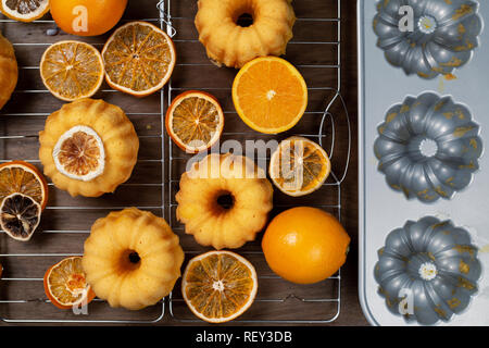 Small orange bundt cakes with fresh and dry oranges on cooling ruck, by backing mould, top view, flat lay - Stock Photo