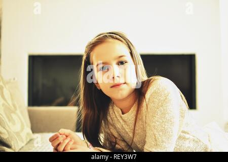 Portrait of a smiling blonde white Caucasian 9 years old girl sitting near a sofa. The child has long hair. Front view, selective focus. - Stock Photo
