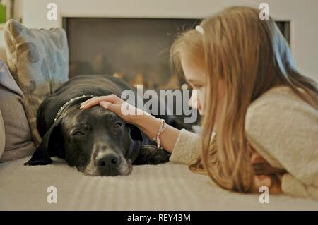 View of a girl child caressing an old black big dog which is lying on the couch. - Stock Photo