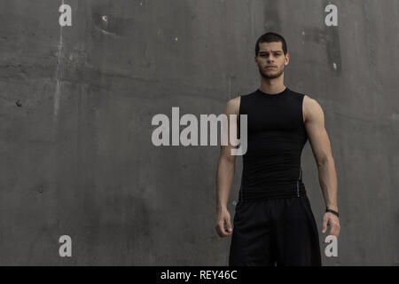 Portrait of athletic muscular young man, in sports clothing, posing on gray industrial background. Fashionable tall male, sport model, muscular body s - Stock Photo
