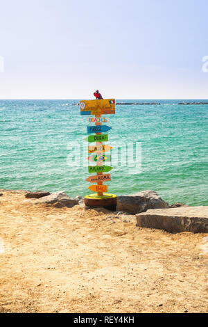 Colorful pole with arrows pointing to place names around the world, on the beach of San Remo in Italy - Stock Photo