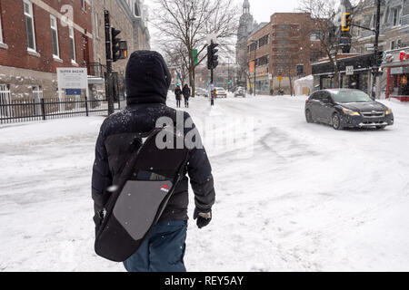 Montreal, Canada - 20 January 2019: Pedestrian walking on Mont-Royal Avenue during snow storm - Stock Photo