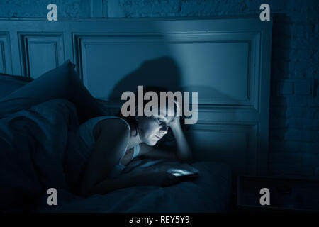 Young attractive woman awake late at night using smart phone lying in bed in a dark bedroom. Using mobile for chatting and sending messages in interne - Stock Photo
