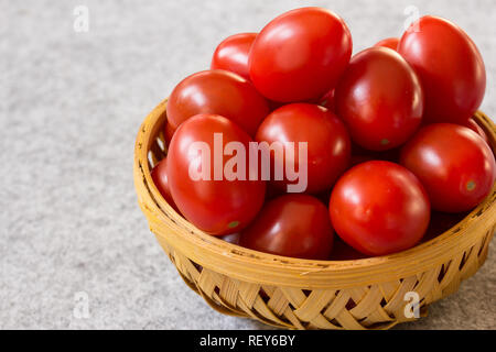 Still life fresh cherry tomatoes in a basket on wooden background, selective focus - Stock Photo