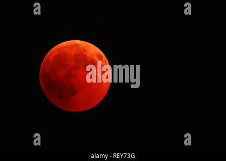 Full red moon over dark black sky background at night. The total phase of the lunar eclipse on July 27, 2018. Moon turning red cause of closer Mars planet to the moon's surface. Copy space. - Stock Photo