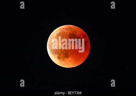 Moon eclipse in full moon and super moon by night. Total Lunar eclipse with moon turning red cause of closer Mars planet. Astronomical background. - Stock Photo