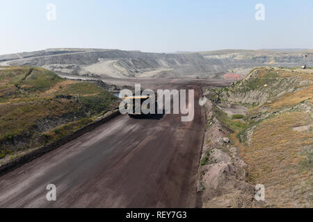 A large coal mining truck hauls coal inside of a vast open pit coal mine in the Powder River Basin of Wyoming, USA. - Stock Photo