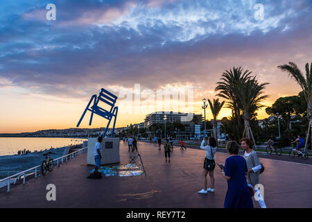 Nice, France - June 23, 2016: Tourists enjoy summer night at Promenade des Anglais in City of Nice, French Riviera. Sculpture of big sea-blue chair (L - Stock Photo