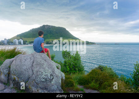 Boy sits on rock on Leisure Island looking out to sea with Mount Maunganui  under evening light and dark clouds in background - Stock Photo