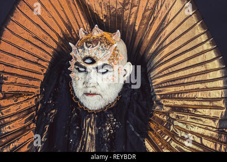 Man with third eye, thorns or warts. Senior man with white beard dressed like monster. Alien, demon, sorcerer makeup. Horror and fantasy concept. Demon with golden collar on black background. - Stock Photo