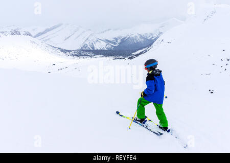 Young skier skiing in the backcountry of a mountain range near Lake Louise in the Canadian Rockies of Alberta, Canada. - Stock Photo