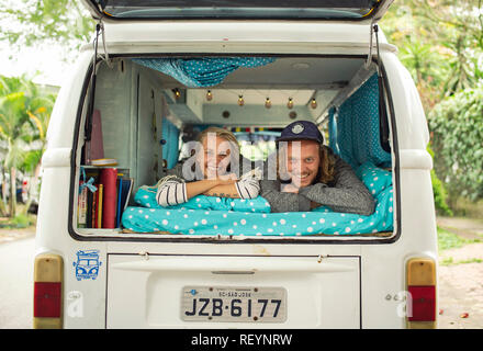 Portrait of a travelling couple in a VW camper van. Van life, travel lifestyle (horizontal portrait, editorial use). Medellín, Colombia. Sep 2018 - Stock Photo