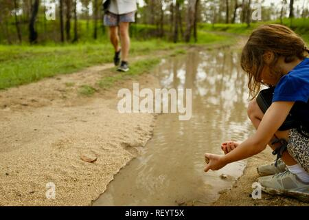 A young girl playing in a muddy puddle on a four wheel drive track through a forest, Mia Mia State Forest, Queensland, Australia - Stock Photo