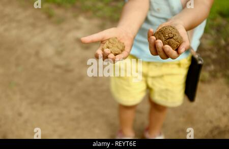 A child holding out balls of mud in her hands, Mia Mia State Forest, Queensland, Australia - Stock Photo