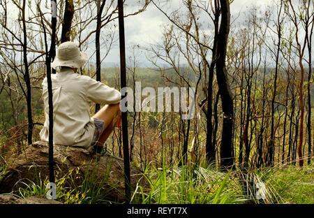 Man sitting on a rock and looking out over the hills, Mia Mia State Forest, Queensland, Australia - Stock Photo