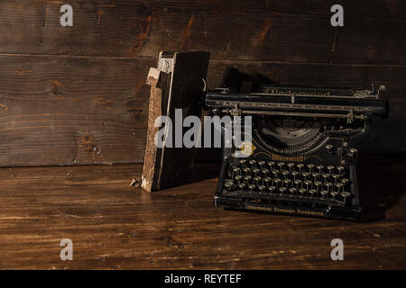 Reading and writing scenes in ancient times: an old book and an old typewriter on a ruined wooden table  on a wooden background