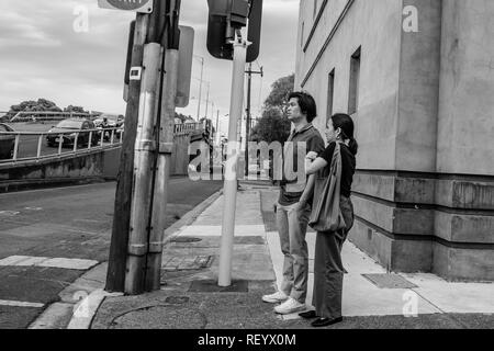 A man and woman stand at a traffic light in the streets of Melbourne, Australia - Stock Photo