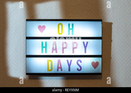 Message Oh Happy Days on illuminated board. Memories and nostalgia concept with text. Daylight from window. Room interior. Colour letters Happy Days o - Stock Photo