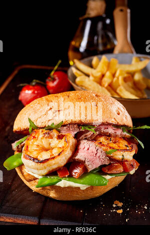 Gourmet Surf and Turf seafood and meat burger with medium rare roast beef, scampi, mangetout peas, rocket and tomato served with potato chips - Stock Photo