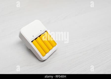 Photo of charger with four yellow batteries on empty grey background - Stock Photo