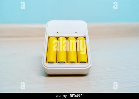Photo of charger with two batteries on empty blue background - Stock Photo