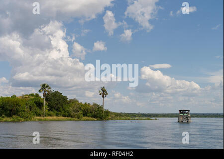 Tourists take a river boat cruise on the Victoria Nile to visit Murchison Falls in Murchison Falls National Park, Uganda with game viewing on the way - Stock Photo