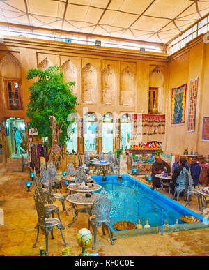 YAZD, IRAN - OCTOBER 18, 2017: The courtyard of medieval mansion is transformed into traditional restaurant with tables around the fountain, on Octobe - Stock Photo