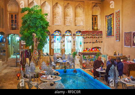YAZD, IRAN - OCTOBER 18, 2017: Interior of the old restaurant, occupying the courtyard of adobe mansion with the fountain among the tables, on October - Stock Photo