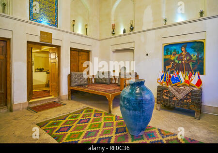 YAZD, IRAN - OCTOBER 18, 2017: The hall of  Tehraniha House ( Fahadan Museum) with old furniture, frescoes, carpets and the entrance to windcatcher (b - Stock Photo