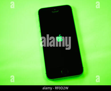 Paris, France - Apr 21, 2016: Newest Apple Computers iPhone SE smartphone after unboxing on green vivid background featuring Apple logotype - Stock Photo