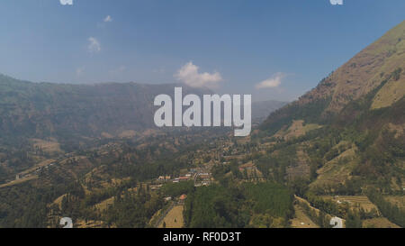 mountains with farmlands, village, fields with crops, trees. Aerial view mountain landscape slopes mountains covered with green forest. Java, Indonesia. - Stock Photo