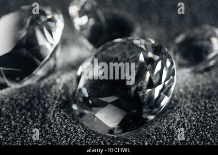 close up of transparent diamonds on grey textured background - Stock Photo