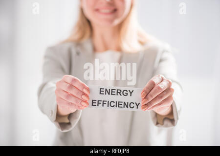 selective focus female hands holding card on white background, energy efficiency concept - Stock Photo