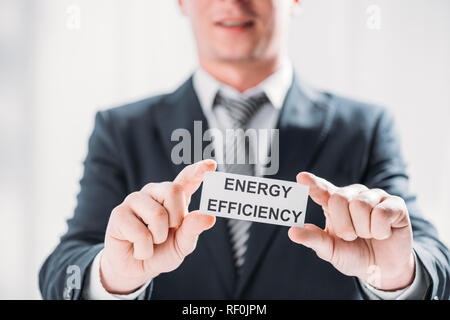 selective focus male hands of businessman holding card with lettering on white background, energy efficiency concept - Stock Photo