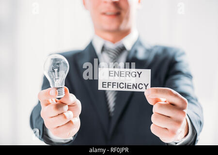 selective focus of card and led lamp in male hands of businessman on white background, energy efficiency concept - Stock Photo