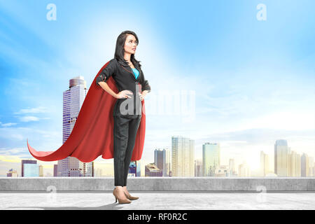 Young asian business woman with red cape standing on the rooftop with cityscapes background - Stock Photo