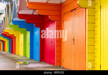 A line of coloured beach huts. A building with a balcony lies beyond and there is a puddle on the concrete floor. - Stock Photo