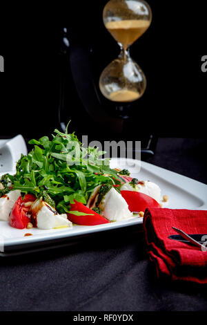 Caprese Italian or Mediterranean salad. Tomato mozzarella basil leaves and olive oil on black table. - Stock Photo