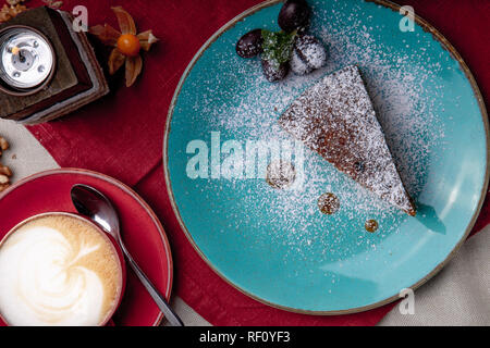 Piece of carrot cake, covered with powdered sugar in a blue plate on a red napkin with cup of coffe and brown sugar - Stock Photo