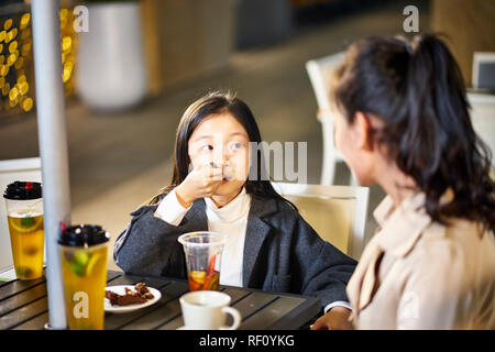 asian mother and daughter talking chatting having drinks and desserts - Stock Photo