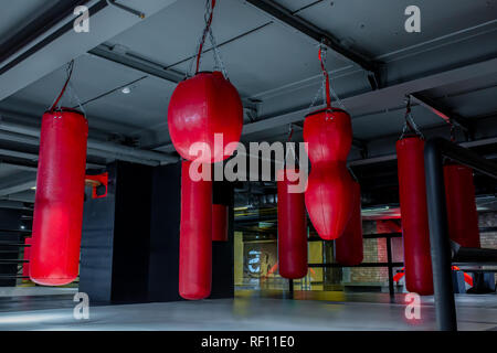 Red punching bags with gym background. Pears for boxing - Stock Photo